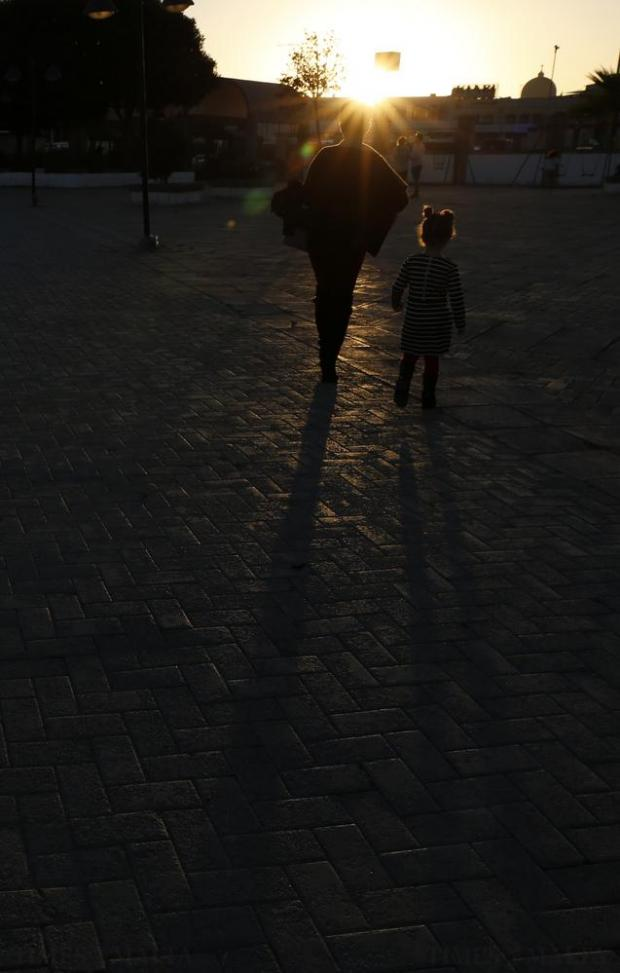 A woman and child leave the Marsa racecourse at sunset on November 13. Photo: Darrin Zammit Lupi