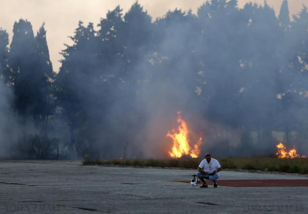 A man tends to his remote-controlled helicopter as a grass fire close to the premises of the Malta Model Aircraft Association in Ta' Qali provides an unusual backdrop to the flying aircraft on August 27. The fire caused no serious damage. Photo: Darrin Zammit Lupi