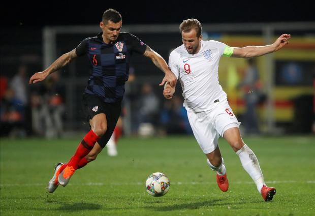 Harry Kane (right) is challenged by Dejan Lovren.