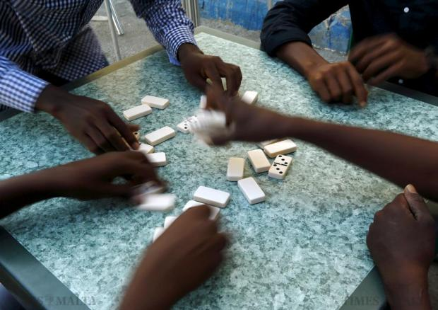 Sub-Saharan African migrants play a game of dominos at a bar in Marsa on June 27. Hours of late-night squabbling in Europe's highest council of state left EU leaders licking political wounds and preparing for weeks of hard bargaining over a plan to cope with a flood of migrants from the south. Photo: Darrin Zammit Lupi