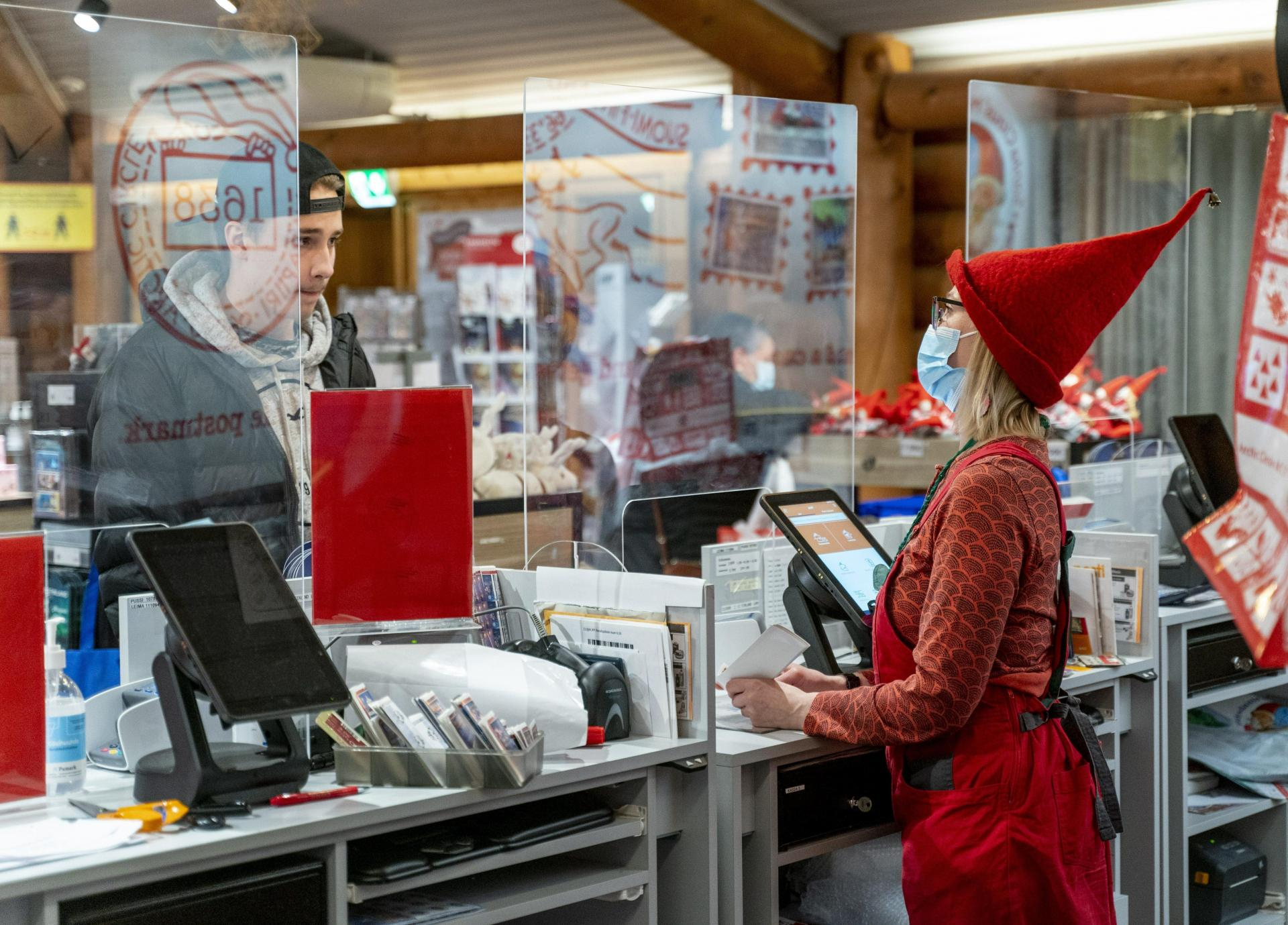 An employee wearing a Christmas hat and face mask to protect against the coronavirus serves a customer through a plexiglass screen at Santa's Main Post Office at Santa Claus Village in the Arctic Circle, Rovaniemi, Finnish Lapland.