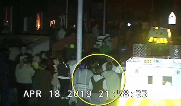 A still image taked from CCTV video footage released by the Police Service of Northern Ireland shows journalist Lyra Mckee (C) highlighted observing violent disorder.