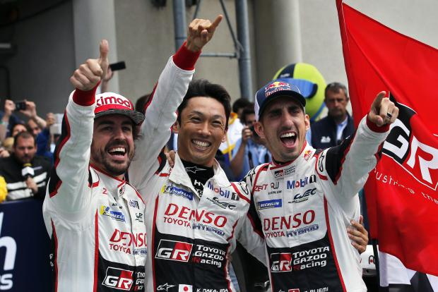 Drivers of the Toyota TS050 Hybrid No8 of the Toyota Gazoo Racing Team Sebastien Buemi of Switzerland, right, Fernando Alonso of Spain, left, and Kazuki Nakajima of Japan, celebrate after winning the 86th 24-hour Le Mans endurance race.