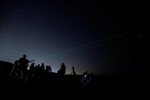 A man points a laser into the sky as people watch the Perseid meteor shower at Dwejra, outside the village of San Lawrenz.