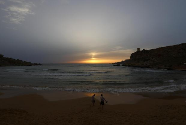 Tourists walk on the sandy beach at Ghajn Tuffieha Bay at sunset on June 17. Photo: Darrin Zammit Lupi