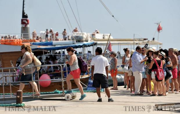Tourists board a boat that will take them to the Blue Lagoon for the day from Bugibba on July 13. Photo: Chris Sant Fournier