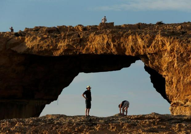 Tourists walk near the Azure Window, a 50 metre high rock arch, at Dwejra Point cliffs on the island of Gozo on September 23. Believed to have been formed millions of years ago, the arch is in danger of collapse due to natural erosion. Photo: Darrin Zammit Lupi