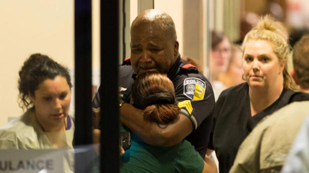 A DART police officer receives comfort at Baylor University Hospital emergency room entrance after the shooting. Photo: Reuters