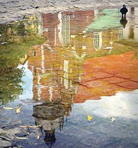A building in Krakow is reflected in a pool of water. Photo: Kazimierz Radziszewska