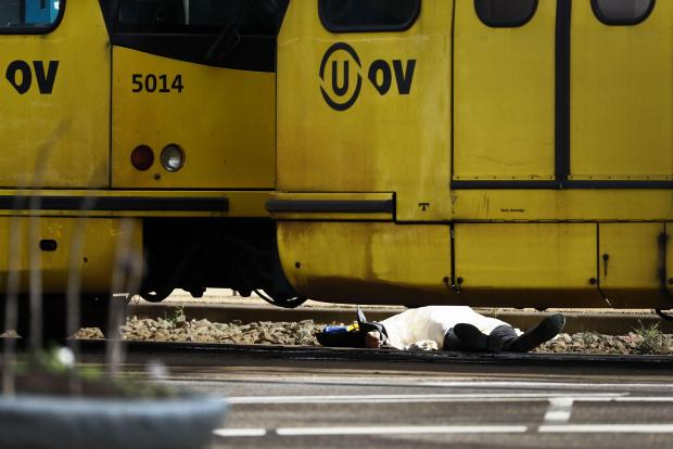 A body lying on the ground is covered near the tram in Utrech. Photo: AFP