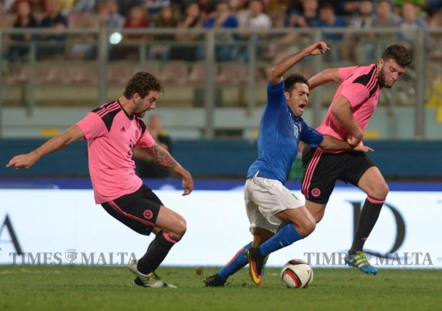 Italy's Eder (centre) is brought down by Scotland's Charlie Mulgrew (left ) and Grant Hanley during their friendly football match at the National Stadium in Ta' Qali on May 29. Photo: Matthew Mirabelli