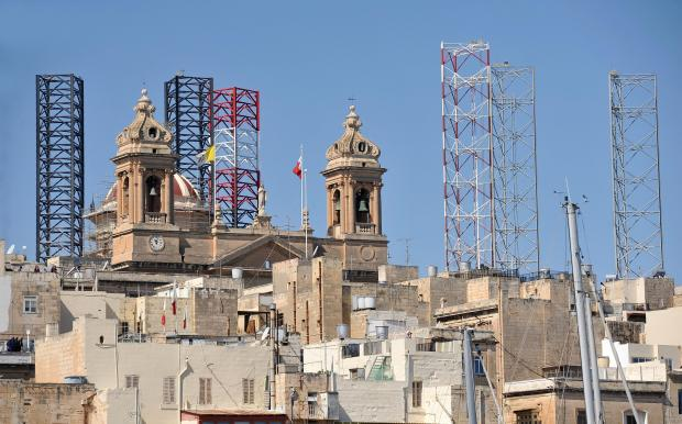 The supporting legs of drilling platforms pop up from behind the Senglea church on March 31. Photo: Chris Sant Fournier