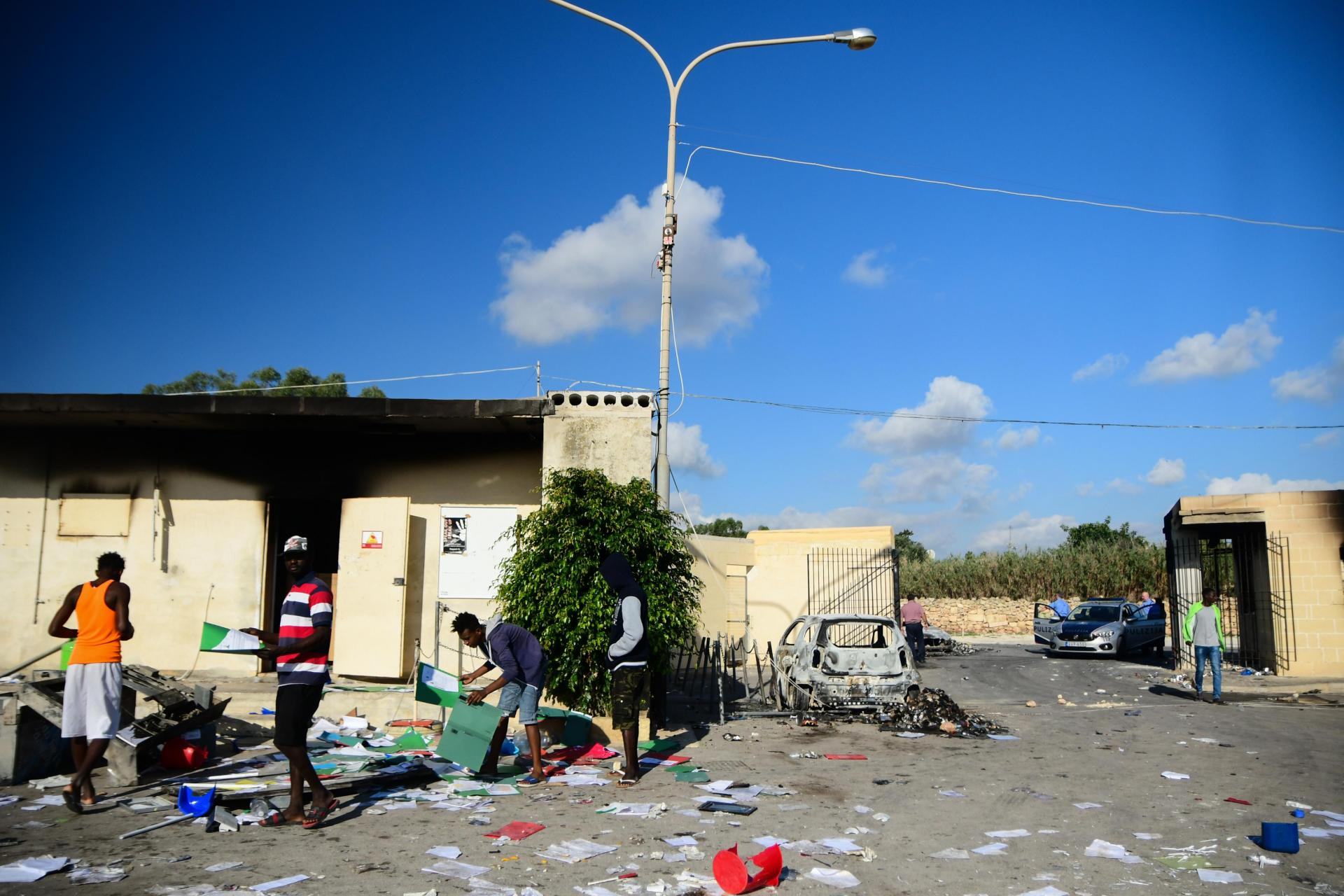 Residents sift through the destruction on Monday following a Sunday night riot at the centre. Photo: Jonathan Borg
