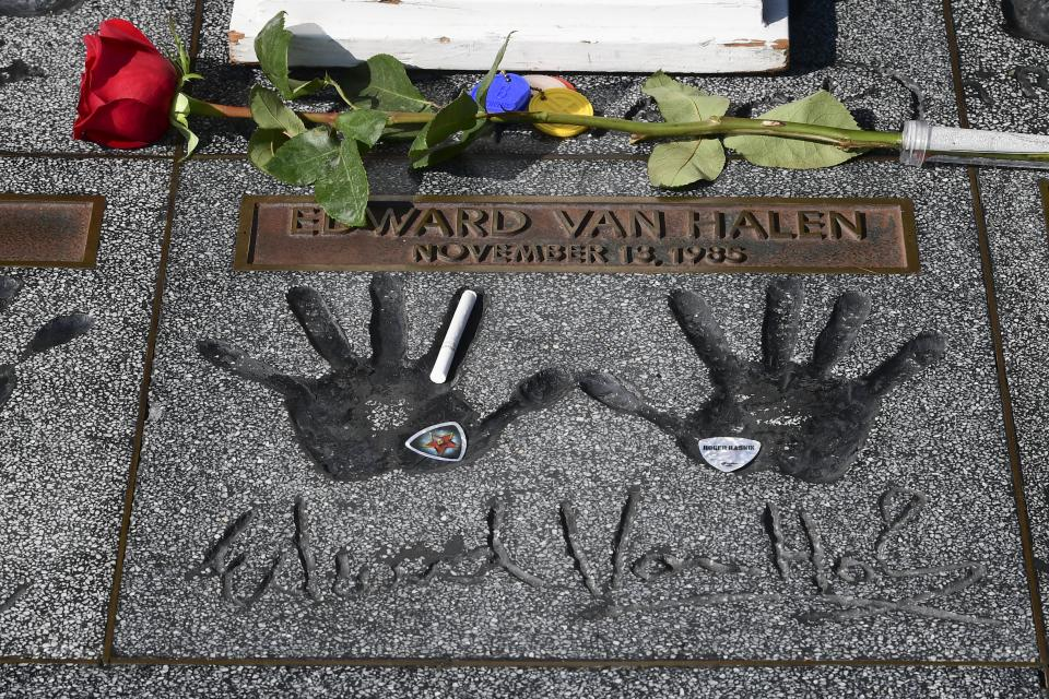 Mementoes including a rose, guitar picks and a cigarette are left on the handprints at the Guitar Center in Hollywood.