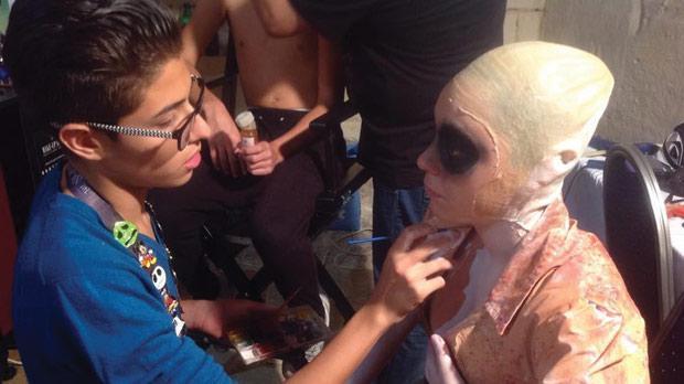 Henry Galea applying make-up on on a model.