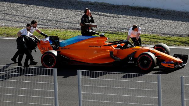 Stoffel Vandoorne's McLaren is pushed away by the teams mechanics in Barcelona.