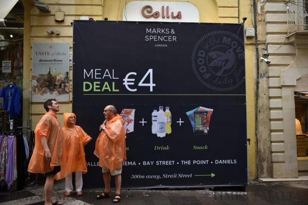Tourists wearing plastic raincoats stand in Republic Street, Valletta next to an advert board on June 6. Photo: Mark Zammit Cordina