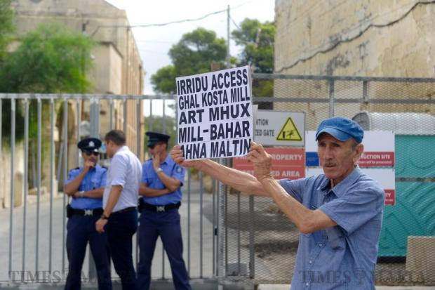 A protestor with a placard reading 'We want access to the foreshore from land and not sea. We are Maltese' stands in front of the Manoel Island gate on September 17. Photo: Steve Zammit Lupi
