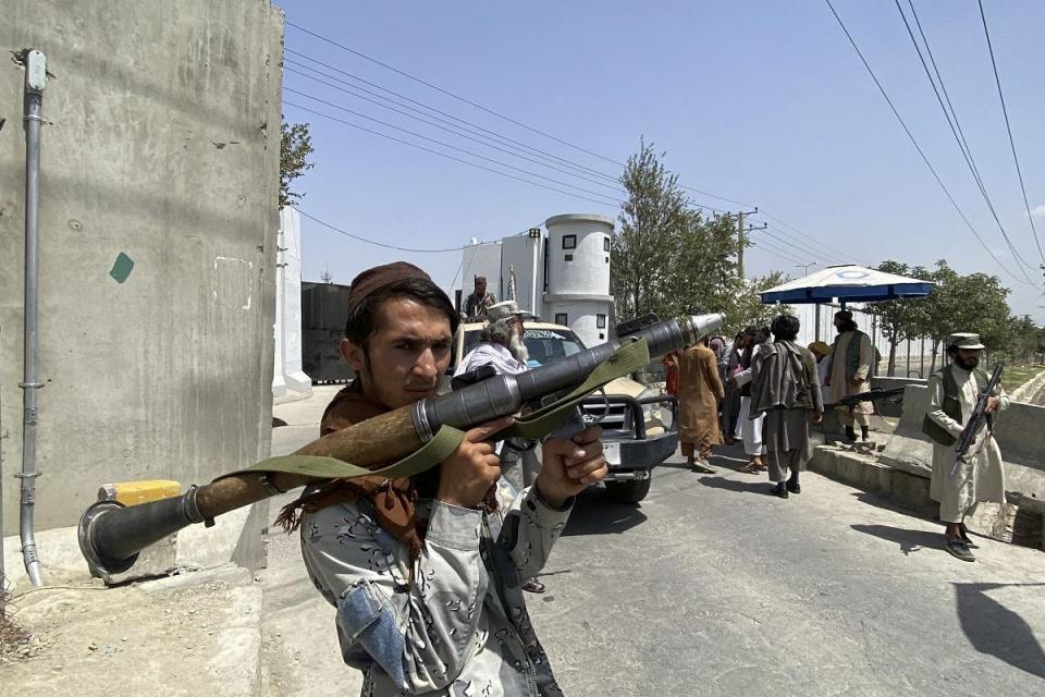 Un combatiente talibán sostiene un cohete RPG mientras hace guardia con otros en una puerta de entrada fuera del Ministerio del Interior en Kabul.  Foto: AFP