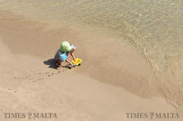 A child plays in the sand on a beach in Sliema on July 13. Photo: Chris Sant Fournier