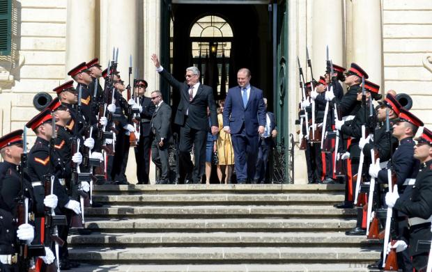 German President Joachim Gauck (left) accompanied by Prime Minister of Malta Joseph Muscat (right) are greeted with applause as they exit Castille in Valletta on April 30. Photo: Matthew Mirabelli