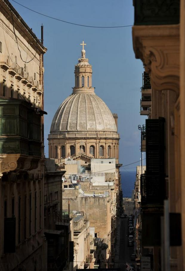 The Carmelite Church is framed between two buildings in Valletta on November 23. Photo: Chris Sant Fournier