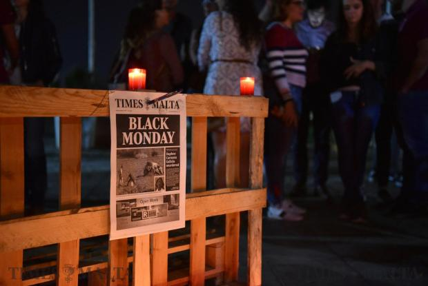 A pen is hammered into a Times of Malta newspaper during a silent candlelight vigil at the University Campus in Tal-Qroqq on October 18 in memory of Journalist Daphne Caruana Galizia who was murdered brutally by a car bomb that week. Photo: Mark Zammit Cordina