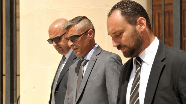 PC Schembri (centre) leaves court with his lawyers in August. Photo: Chris Sant Fournier