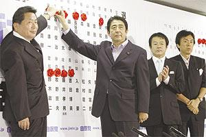 Japanese Prime Minister Shinzo Abe (second from left) puts a rose on the name of a candidate who is expected to be elected in the upper house election during a live TV appearance at his Liberal Democratic Party headquarters in Tokyo, yesterday, after an upper house election.