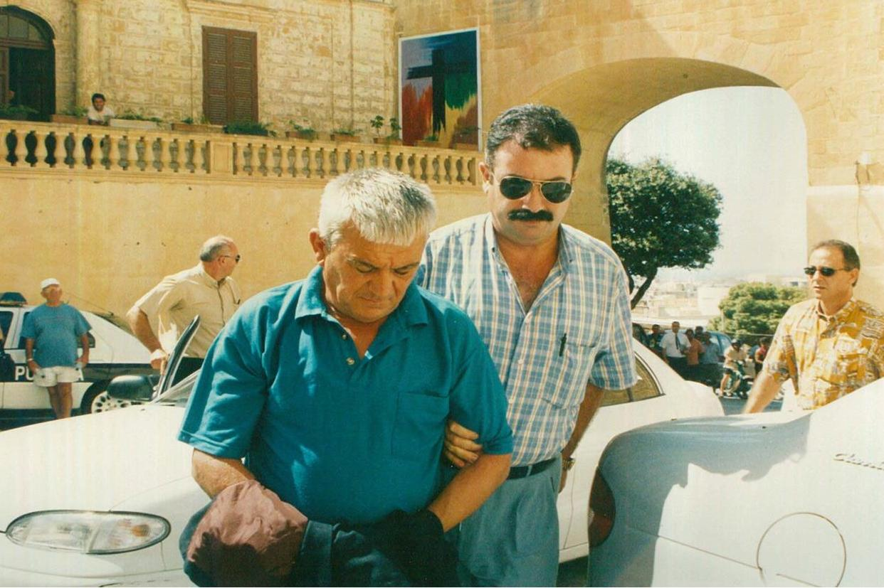 John Attard (left) being escorted by police into the Gozo court house. Photo: L-Orizzont