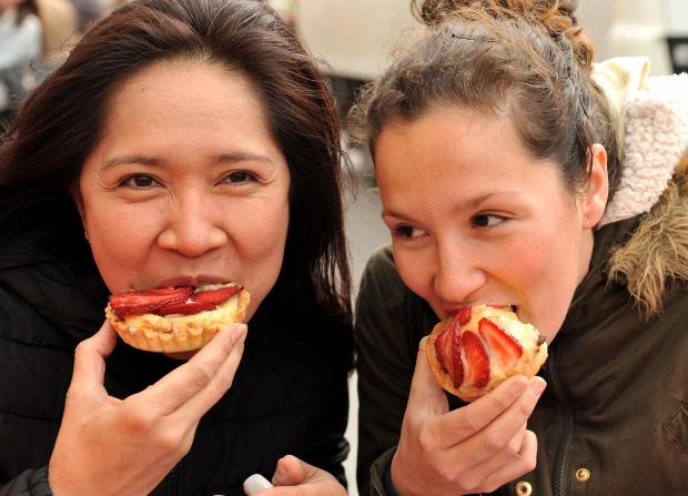 Tourists bite into a strawberry tart at the Mgarr Strawberry Festival on April 2. Photo: Chris Sant Fournier