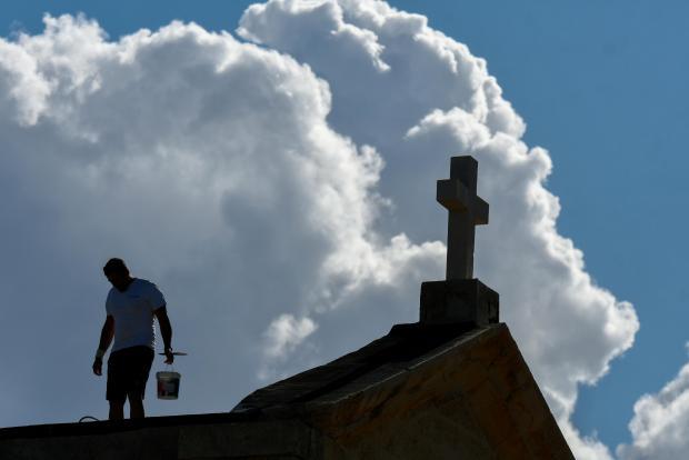 A man works on the roof of a Karkara chapel.JPG skyline on October 11. Photo: Jonathan Borg