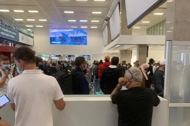 Hundreds queue for COVID-19 checks at airport arrivals hall