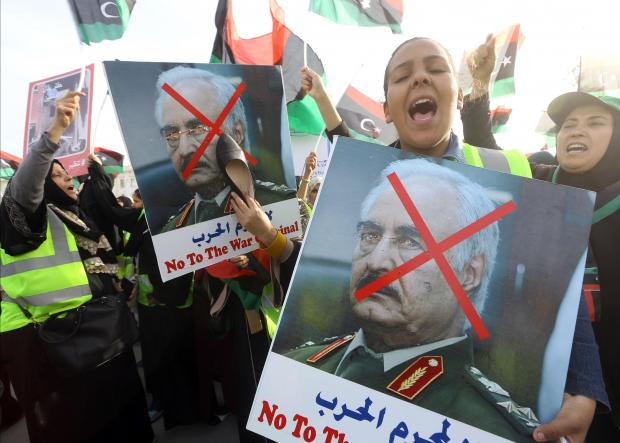 A Libyan woman hits a portrait of strongman Khalifa Haftar with a shoe during a demonstration against him in the capital Tripoli's Martyrs Square.