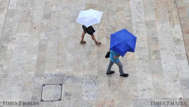 A couple of people take cover from the storm in Republic Street Valletta on September 9. Photo: Chris Sant Fournier