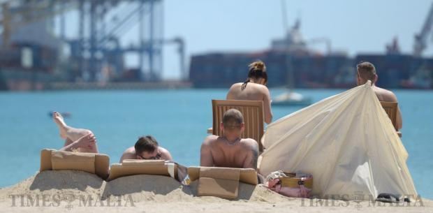 Tourists enjoy the sun at Pretty Bay in Birzebugia on April 11. Photo: Matthew Mirabelli