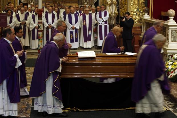A priest lays his hand on the coffin of Archbishop Emeritus Joseph Mercieca at the start of his funeral Mass at St John's Co-Cathedral in Valletta on March 23. Photo: Darrin Zammit Lupi