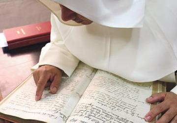 A Dominican friar going through a baptismal register.