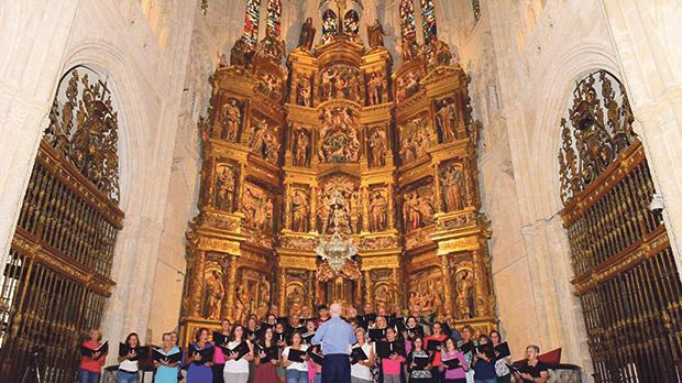 Photos show the choir singing at the Cathedral of Santiago de Compostela.