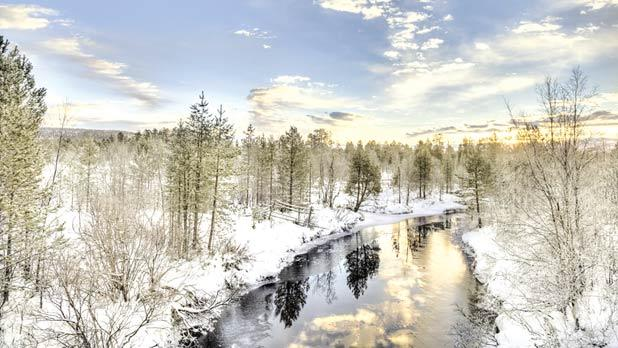 A lake flowing in the frozen landscape in Inari, Lapland, Finland.