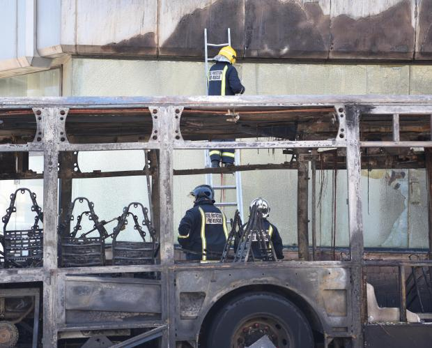 Firefighters break damaged glass due to a severe fire that broke out on a public bus in St Pauls bay on May 04. Photo: Mark Zammit Cordina