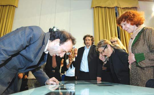 Roberto Benigni marvelling over artist Monika Beisner's (right)illustrations at the Italian Cultural Institute. Photo: Matthew Mirabelli.