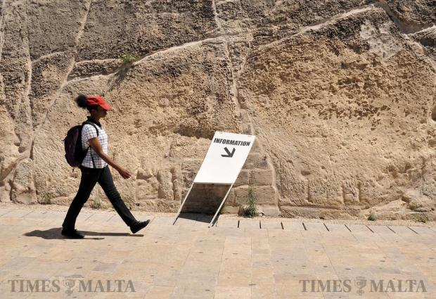 A woman walks past an information sign that points nowhere at the Valletta bus terminus on August 29. Photo: Chris Sant Fournier