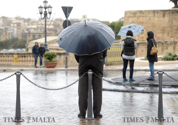 A man waits for a car sheltering from the rain under his umbrella on the first of Spring in Valletta on March 21. Photo: Matthew Mirabelli