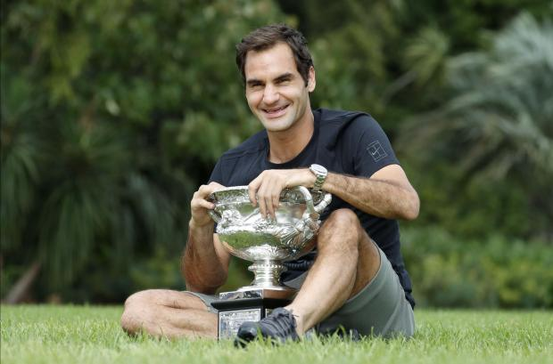 Roger Federer of Switzerland poses with the men's singles trophy during the winner's photoshoot at the government house in Melbourne.