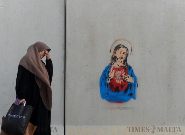 A Muslim women walks by a street stencil portraying Jesus Christ with a euro sign at the Valletta bus terminus on October 11. Photo: Steve Zammit Lupi