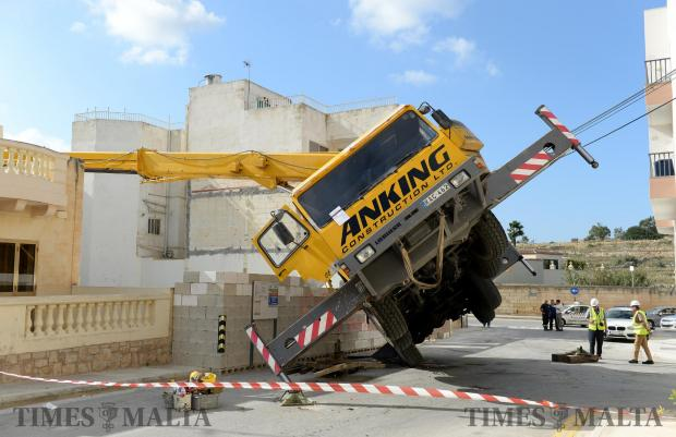 A toppled crane balances precariously after the road underneath one of its legs collapsed in Bahar ic-Caghaq on October 30. Photo: Matthew Mirabelli