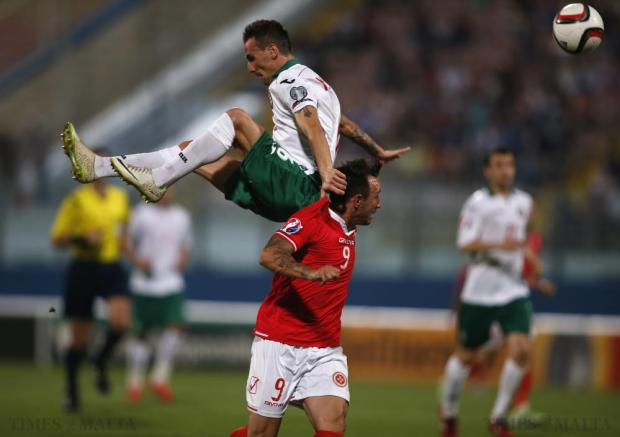 Bulgaria's Yordan Minev (top) jumps high for the ball over Malta's Michael Mifsud during their Euro 2016 Group H qualification soccer match at the National Stadium in Ta' Qali on June 12. Photo: Darrin Zammit Lupi