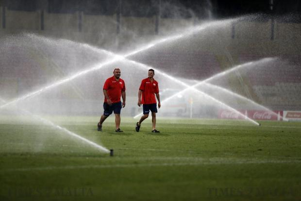 Ground staff walk on the pitch as the turf is watered by sprinklers in between matches at the National Stadium in Ta' Qali on September 10. Photo: Darrin Zammit Lupi
