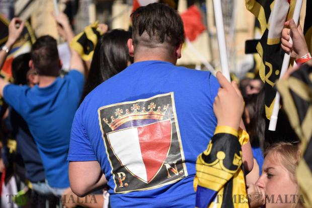 A man wears a blue shirt with a large Nationalist party emblem printed on the back during a mass meeting in Zabbar on May 21. Photo: Mark Zammit Cordina